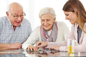 Glückliches Paar Senioren spielt Puzzle mit der Enkelin